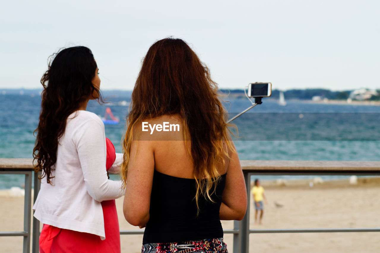 Female friends taking selfie while standing by railing at beach against clear sky