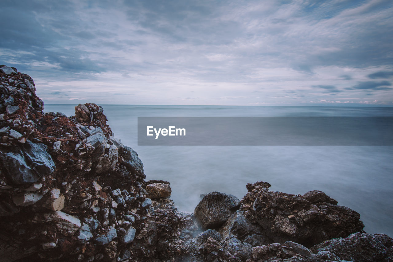 sky, sea, water, cloud - sky, rock, rock - object, tranquility, scenics - nature, beauty in nature, solid, tranquil scene, nature, no people, horizon over water, horizon, rock formation, beach, idyllic, land, outdoors, rocky coastline, eroded