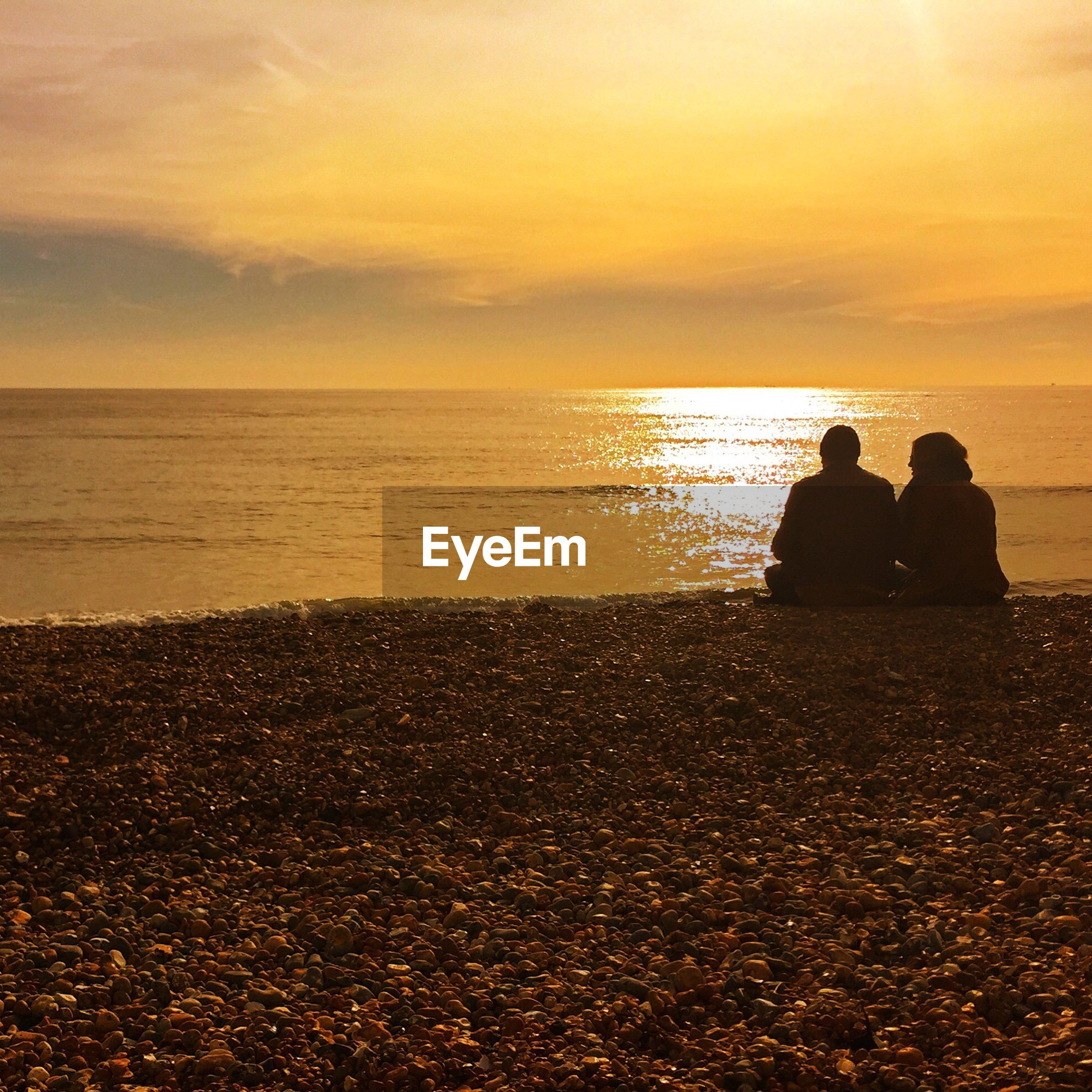 Rear view of man and woman sitting at seaside during sunrise