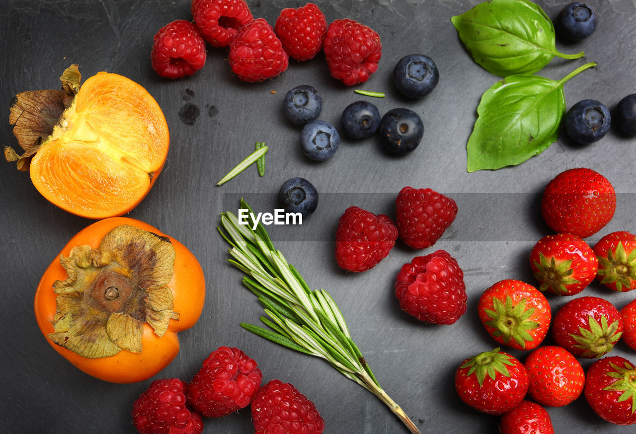 HIGH ANGLE VIEW OF STRAWBERRIES AND FRUITS IN CONTAINER