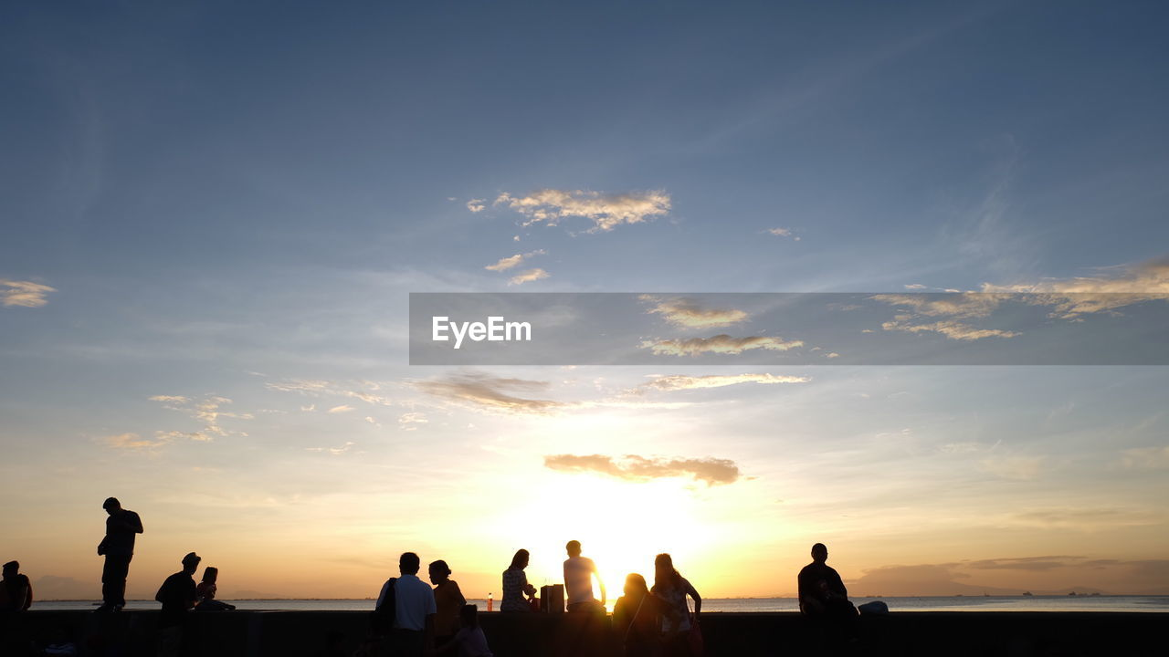 SILHOUETTE MEN AGAINST SKY AT SUNSET