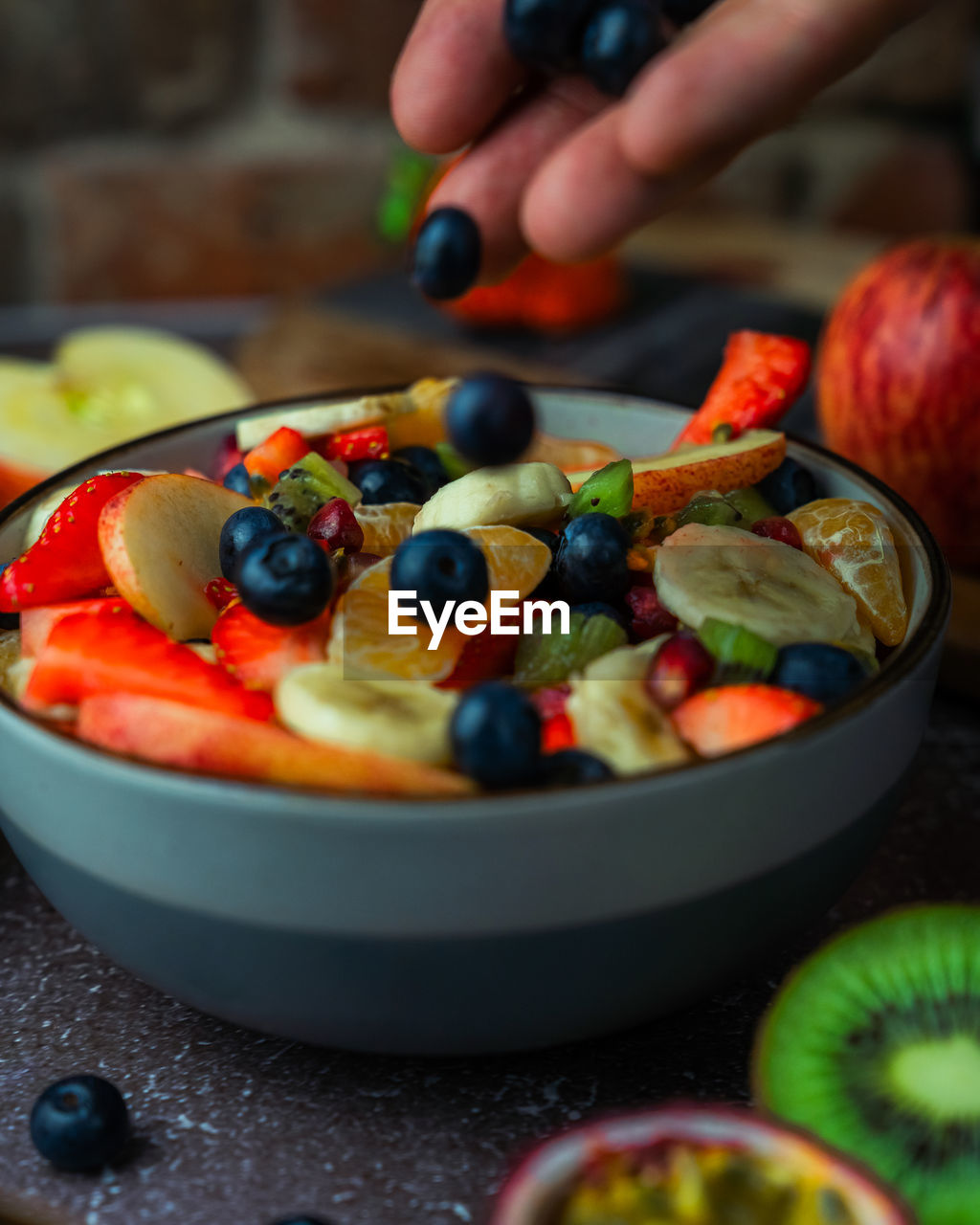 Close-up of hand adding fruit to fruit salad in bowl on table