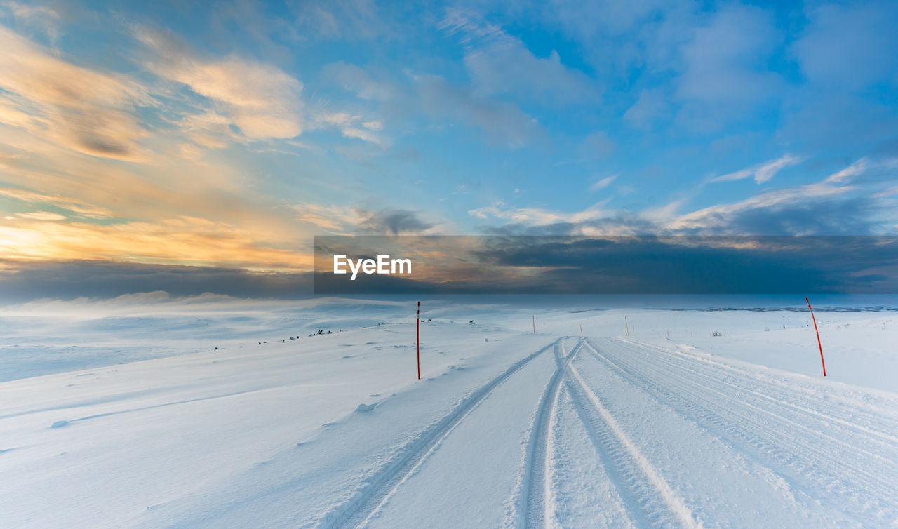 cold temperature, snow, winter, cloud - sky, sky, scenics - nature, white color, environment, beauty in nature, transportation, tranquil scene, nature, non-urban scene, covering, tranquility, direction, landscape, no people, the way forward, diminishing perspective
