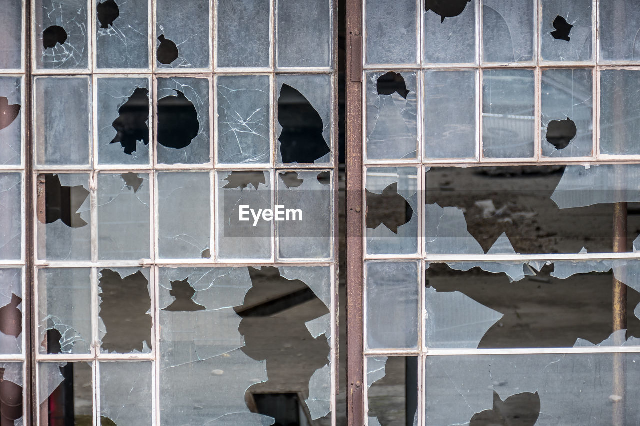 window, architecture, built structure, damaged, full frame, no people, day, glass - material, building, broken, pattern, backgrounds, outdoors, metal, building exterior, destruction, transparent, security, close-up, abandoned