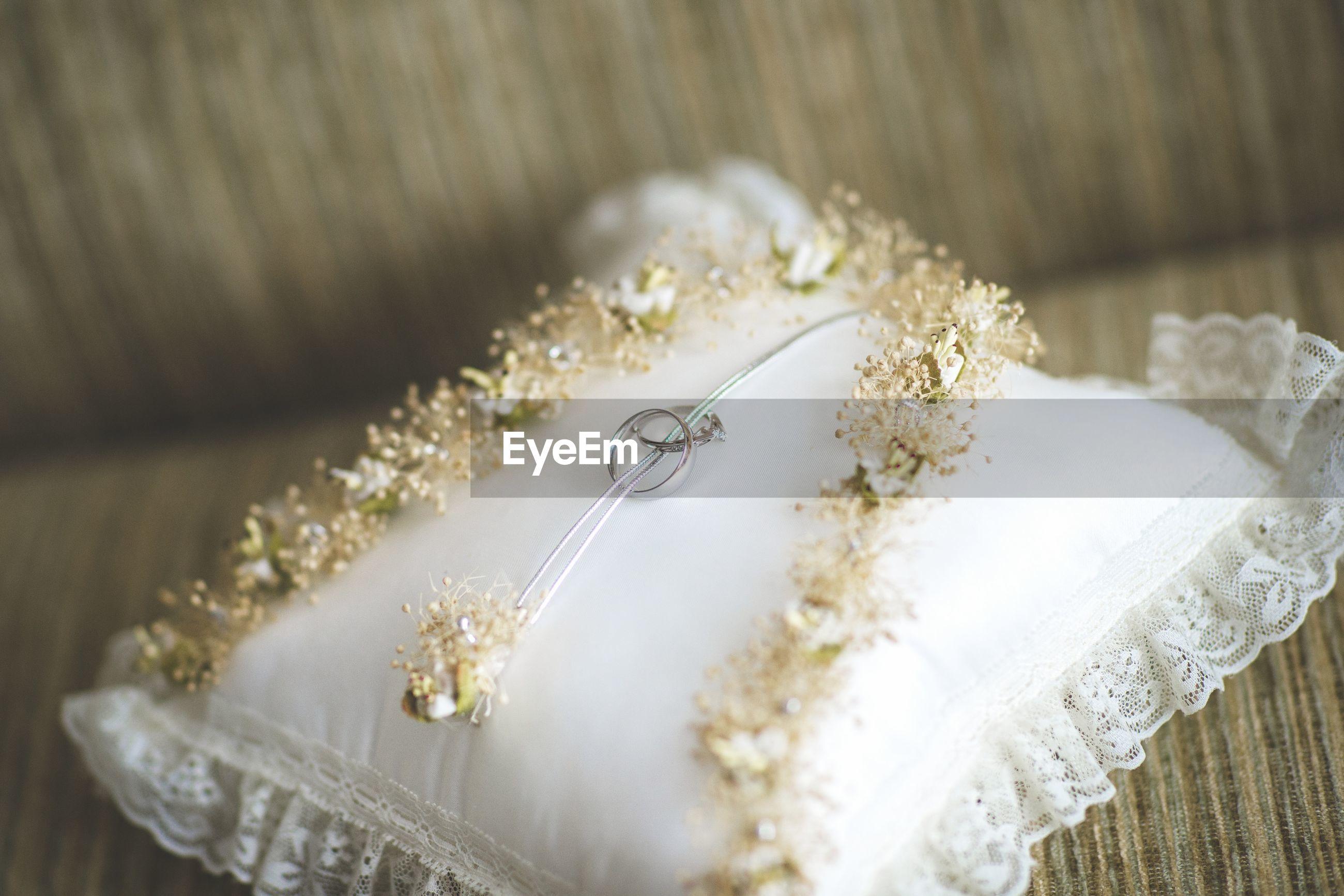 High angle view of wedding rings on sofa