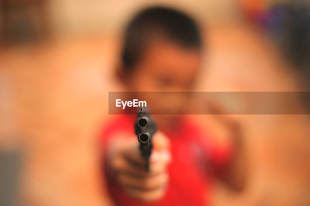 Close-Up Of Boy Shooting With Toy Gun