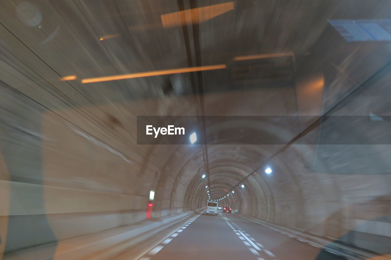 transportation, illuminated, the way forward, architecture, direction, tunnel, indoors, built structure, motion, diminishing perspective, road, glass - material, lighting equipment, mode of transportation, transparent, car, sign, road marking, motor vehicle, no people, ceiling, light at the end of the tunnel