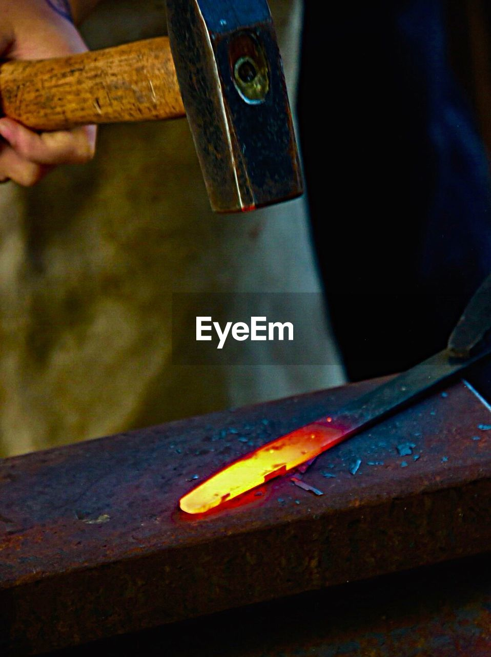 one person, human hand, workshop, hand, heat - temperature, working, burning, metal, fire, indoors, work tool, blacksmith, holding, occupation, flame, art and craft, human body part, metal industry, tool, craft, skill, sparks, iron - metal