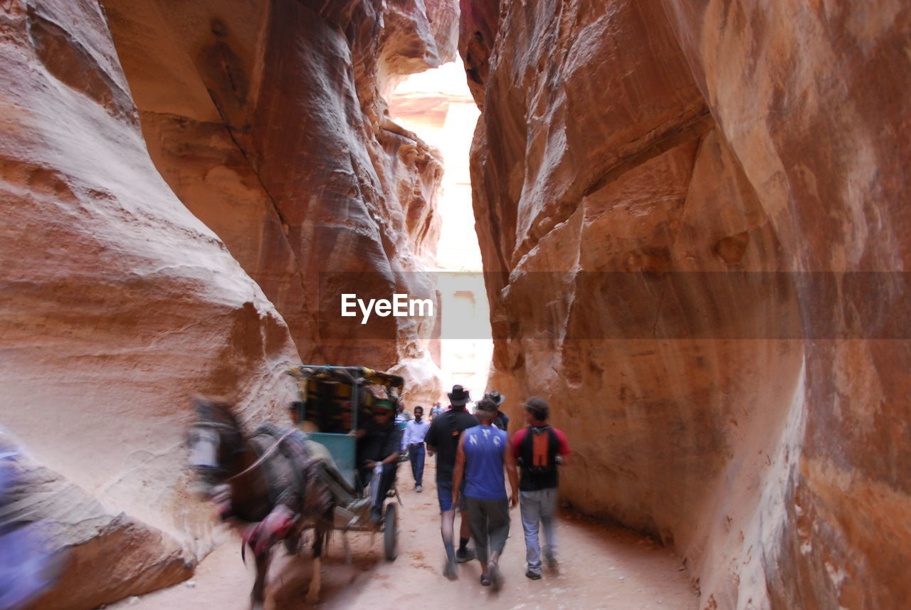 REAR VIEW OF PEOPLE WALKING ON CAVE
