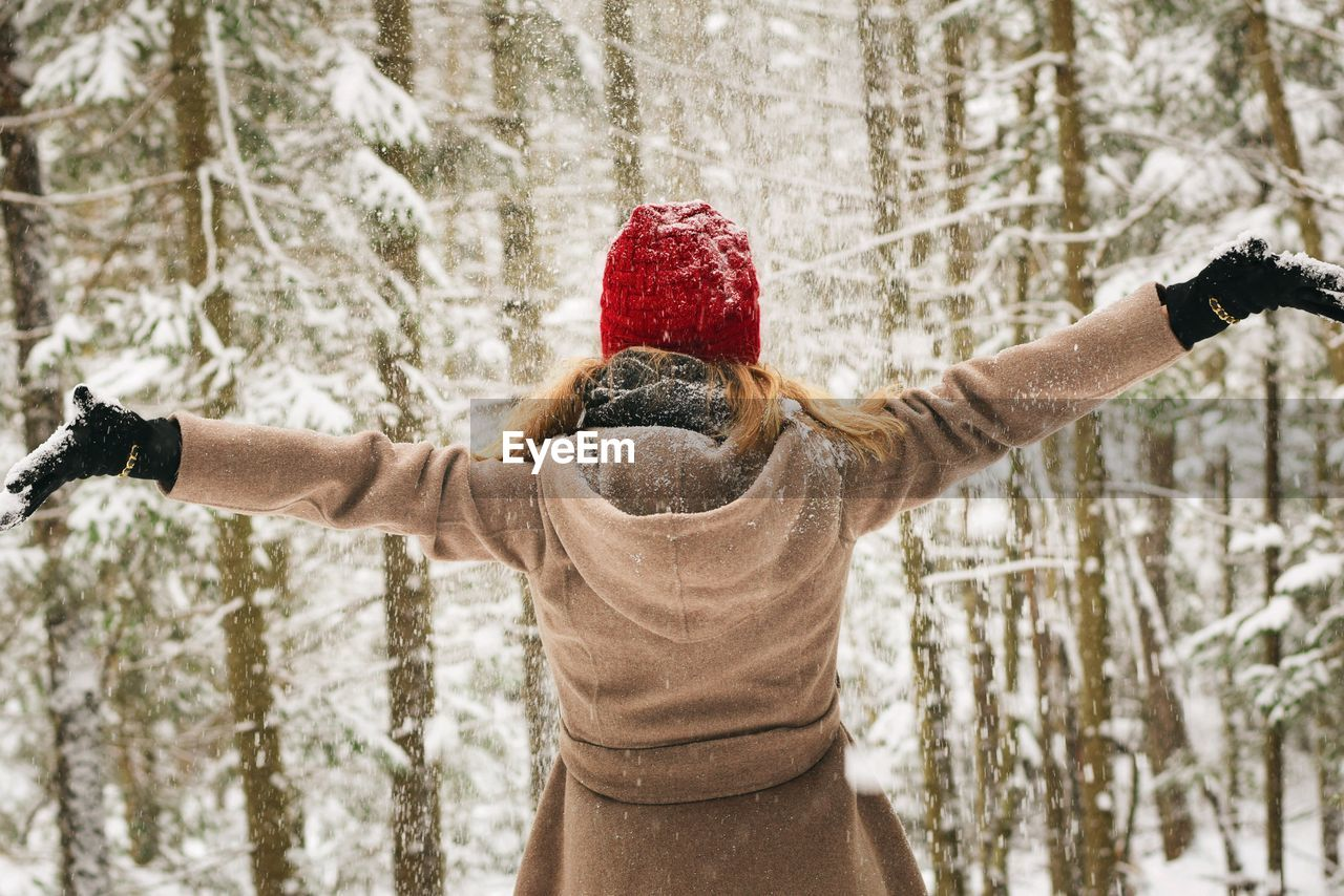Rear view of woman with arms outstretched standing in forest during winter