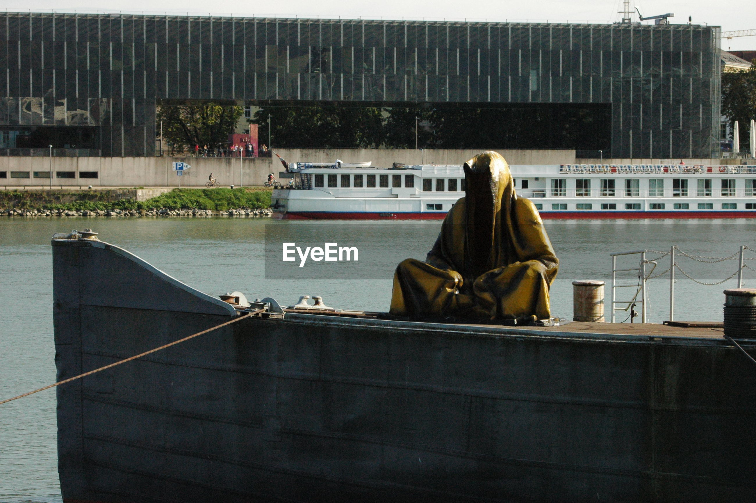 REAR VIEW OF MAN SITTING ON BOAT AGAINST RIVER
