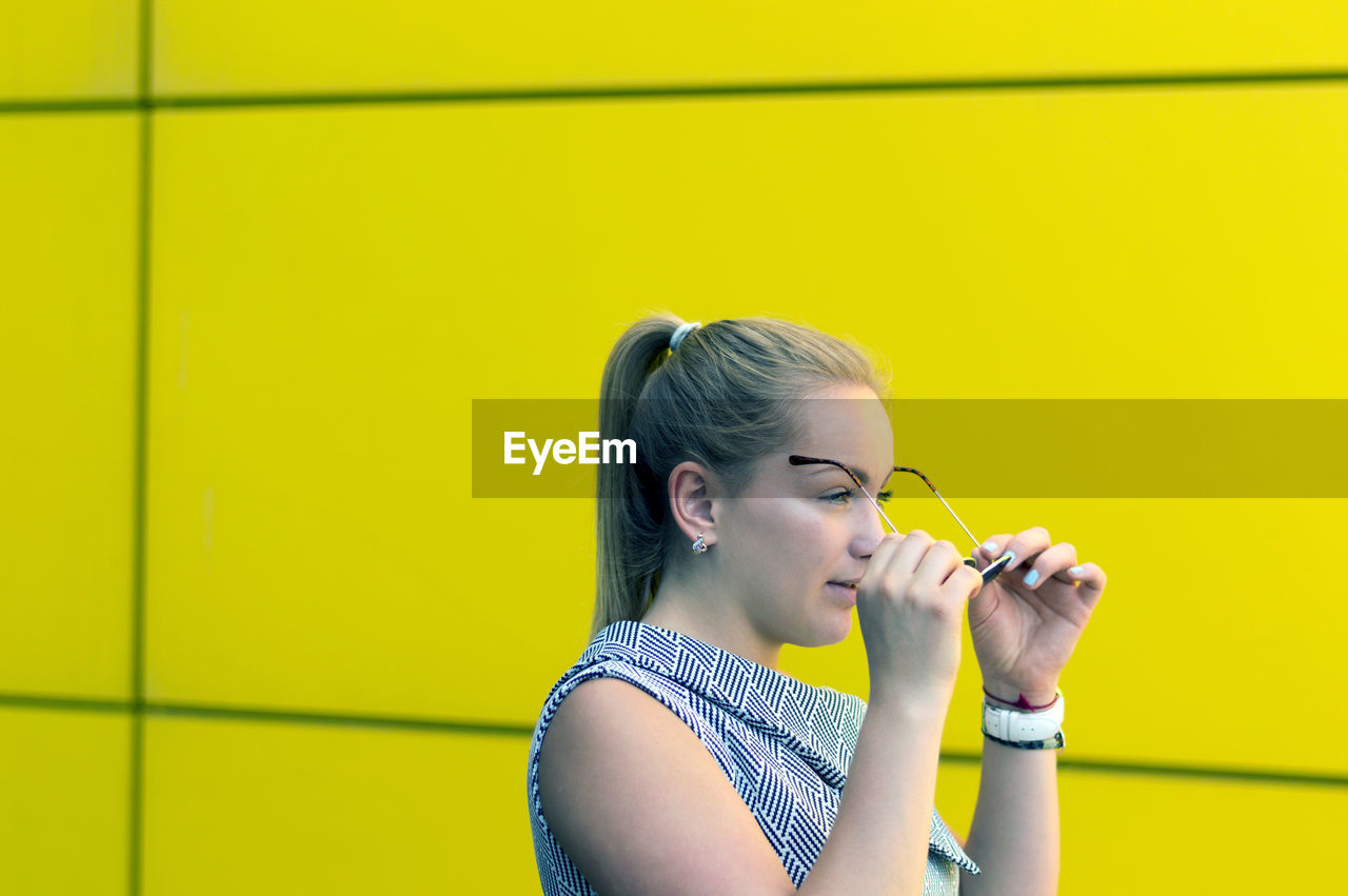 Woman wearing eyeglasses by yellow wall
