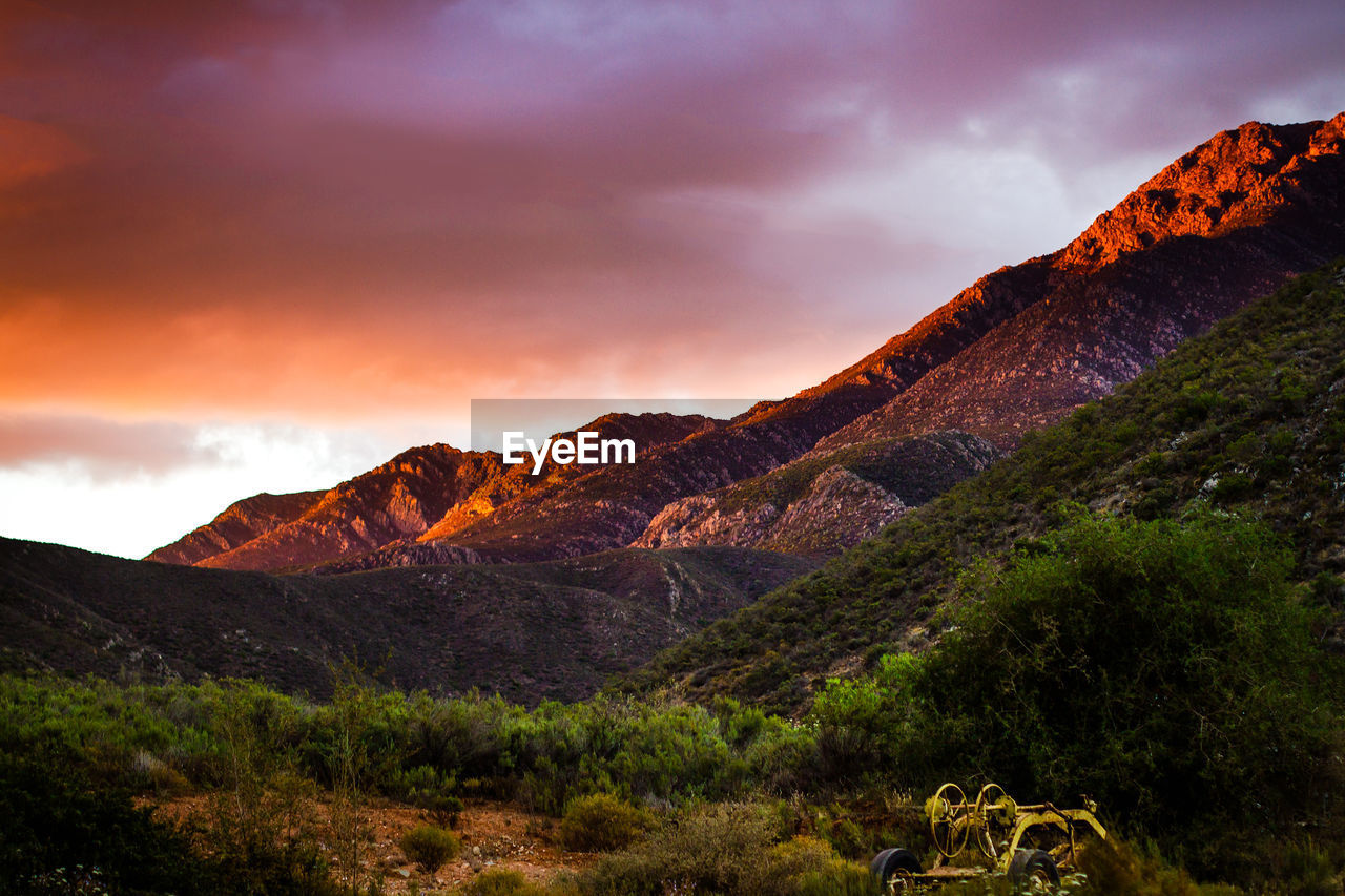mountain, sky, scenics - nature, cloud - sky, beauty in nature, tranquil scene, environment, tranquility, non-urban scene, landscape, mountain range, nature, no people, sunset, remote, idyllic, geology, rock, plant, rock - object, outdoors, arid climate, formation, climate