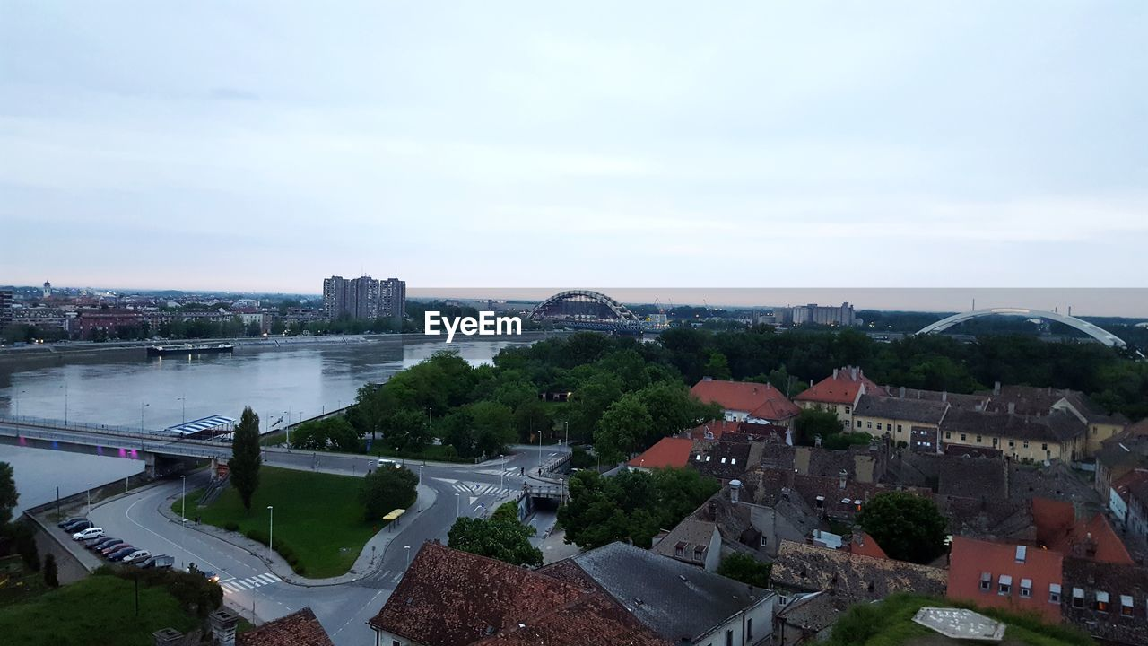 architecture, built structure, building exterior, sky, city, water, cloud - sky, cityscape, nature, connection, river, building, day, residential district, high angle view, no people, bridge, plant, tree, outdoors, bridge - man made structure, arch bridge