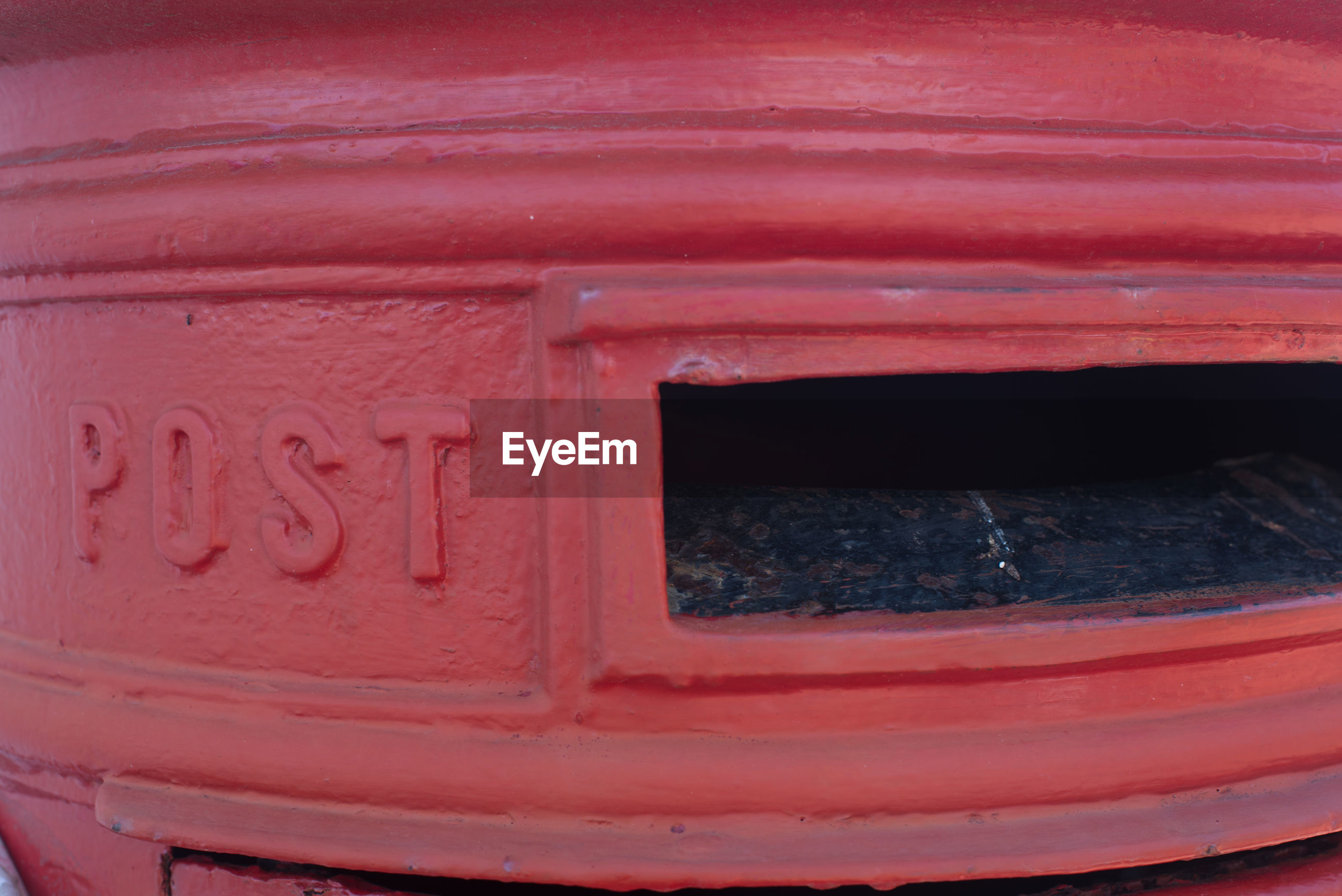 Close-up of text on red public mailbox