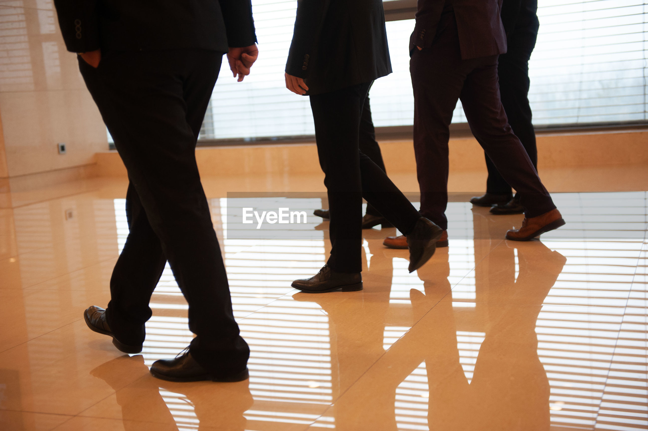 Low section of business people walking on floor