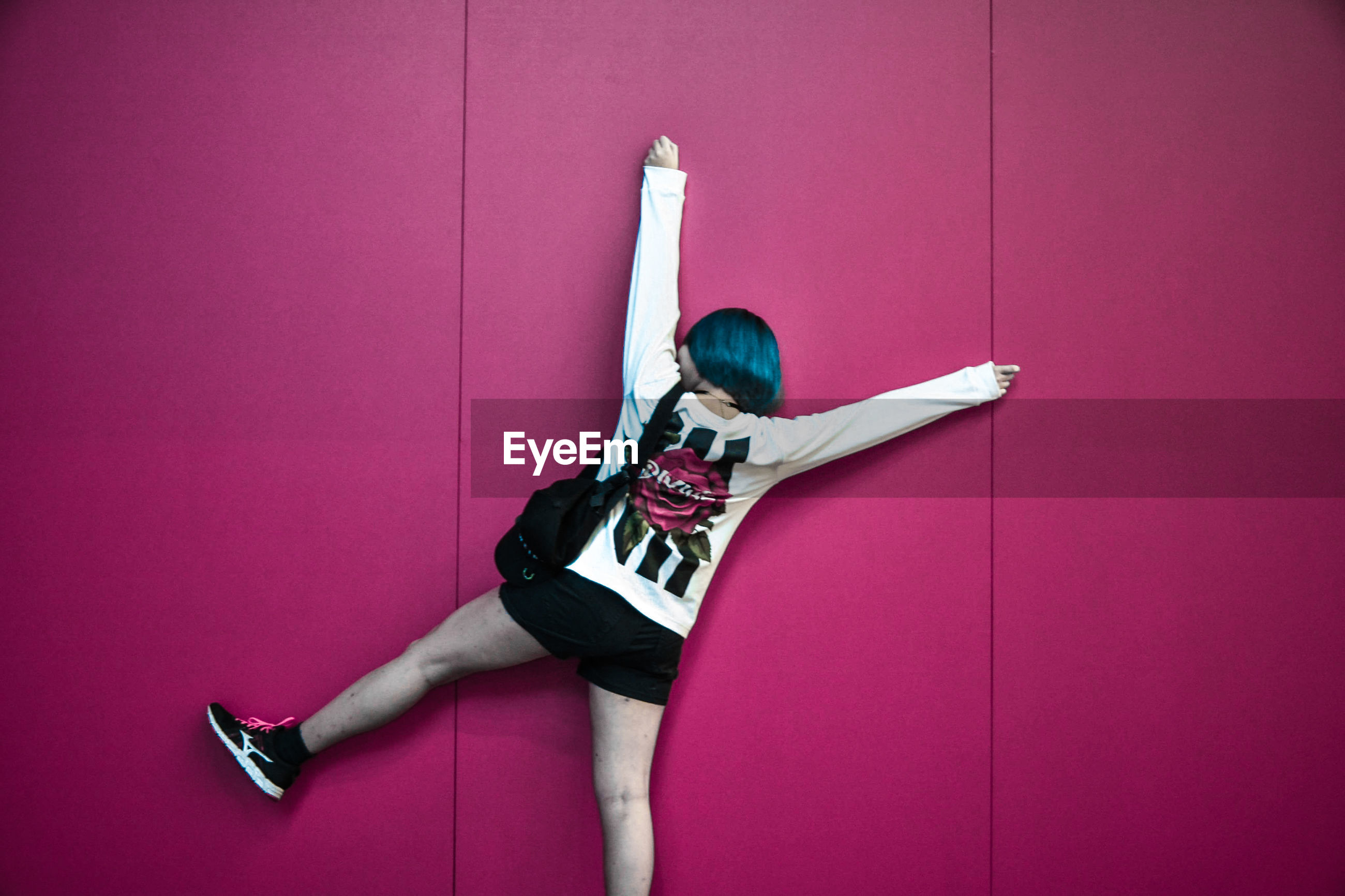 HIGH ANGLE VIEW OF WOMAN WITH PINK WALL