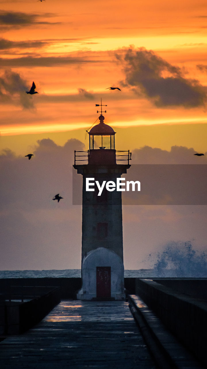sunset, sky, built structure, architecture, cloud - sky, orange color, sea, water, building exterior, lighthouse, tower, nature, beauty in nature, scenics - nature, bird, direction, building, pier, horizon over water, guidance, no people