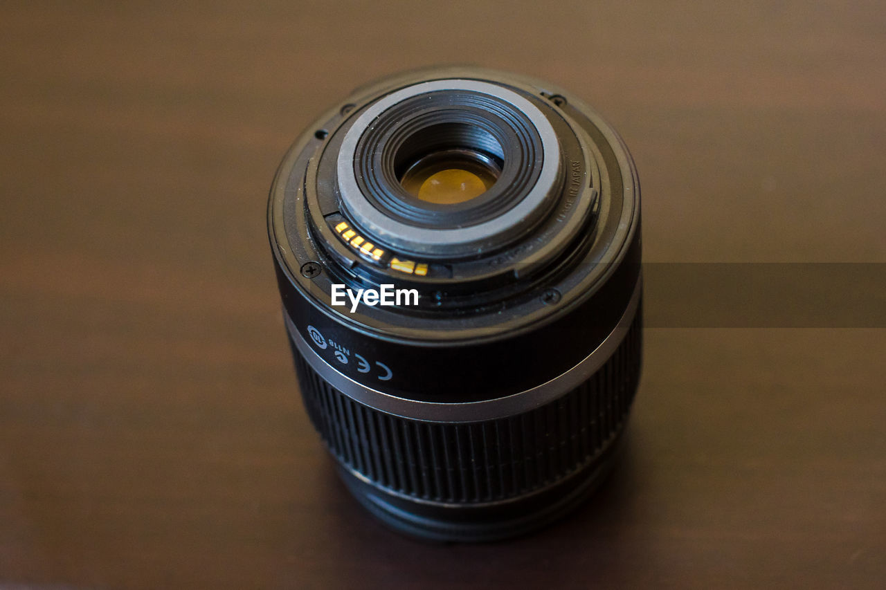 photography themes, camera - photographic equipment, table, lens - optical instrument, technology, photographic equipment, indoors, close-up, no people, still life, focus on foreground, high angle view, single object, film industry, rolled up, circle, camera, geometric shape, shape, glass - material, digital camera, silver colored