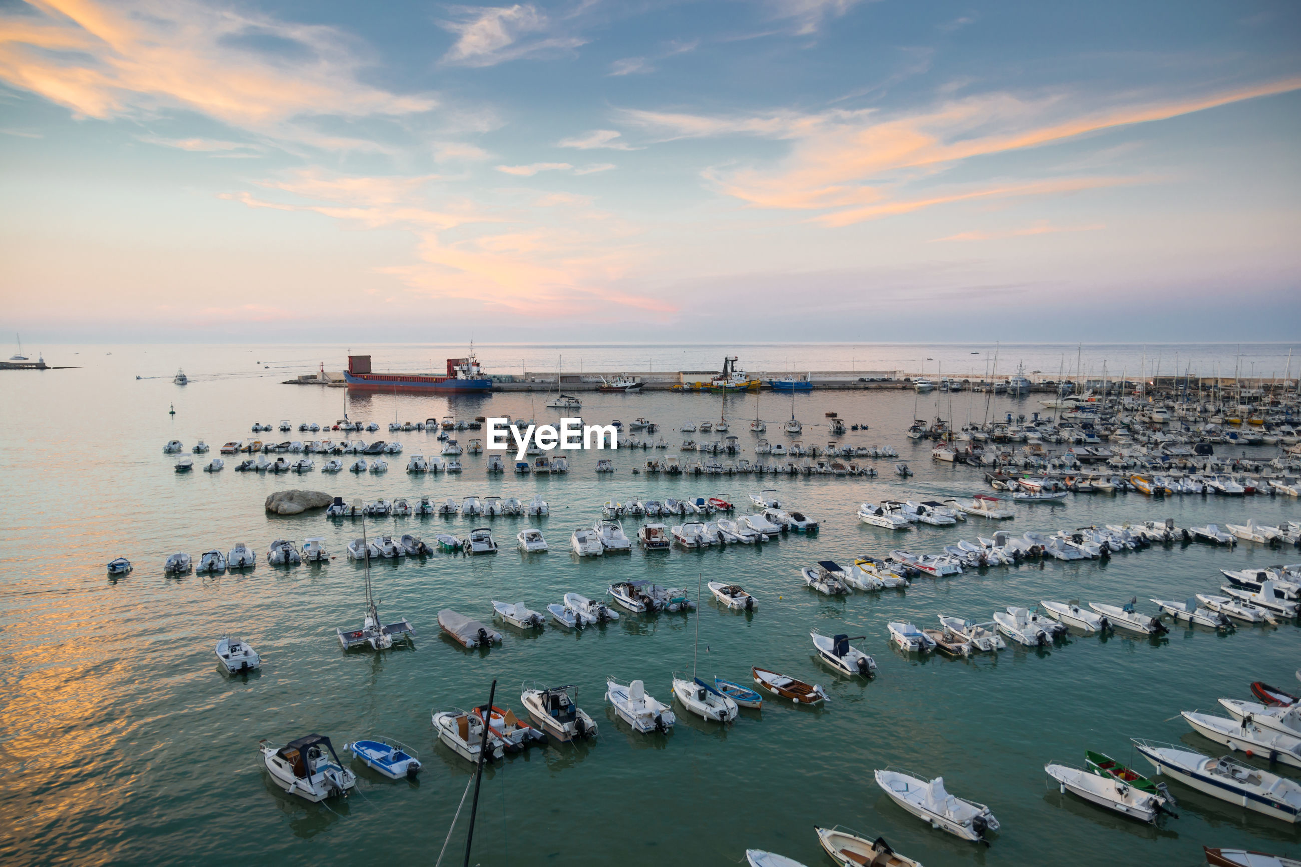 Aerial view of sailboats moored in sea against sky during sunset