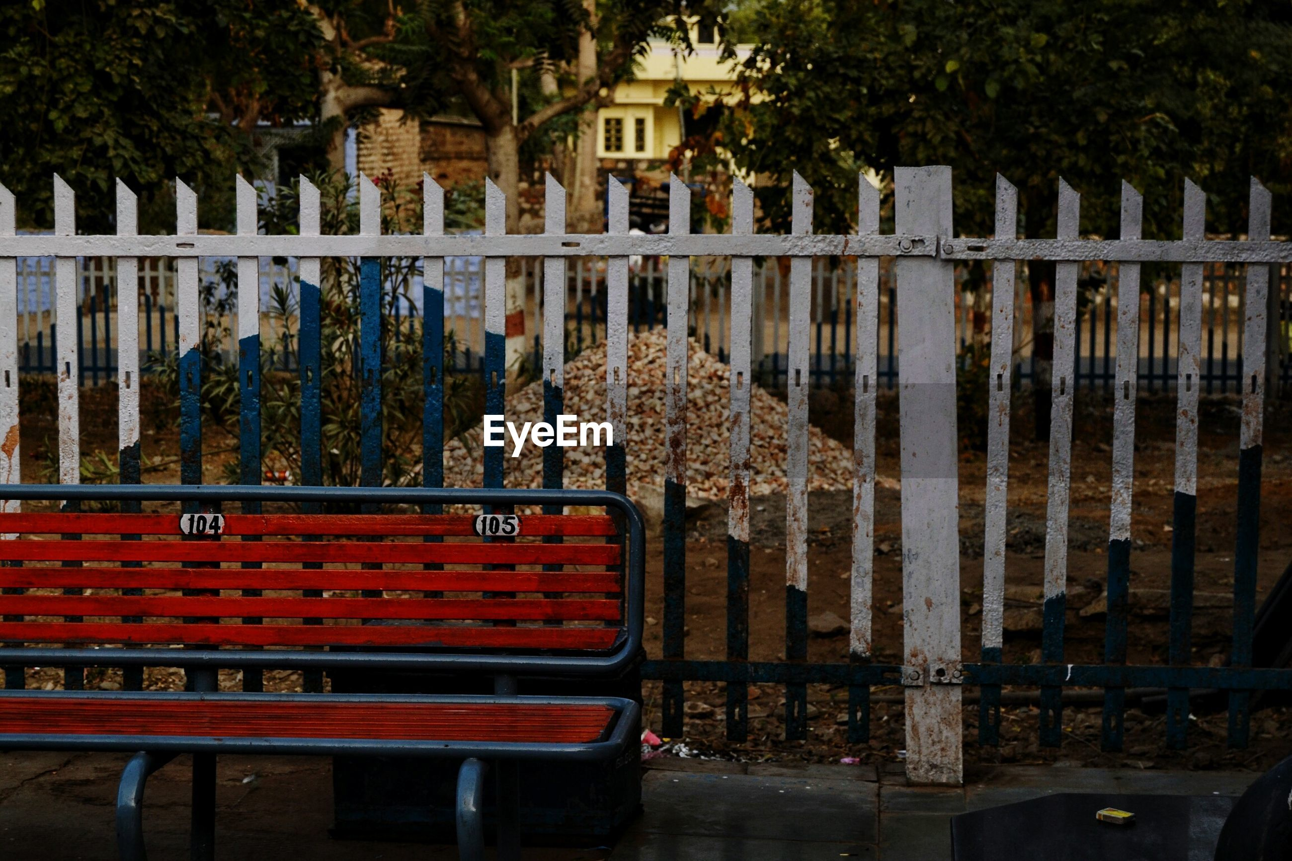 Empty bench by fence