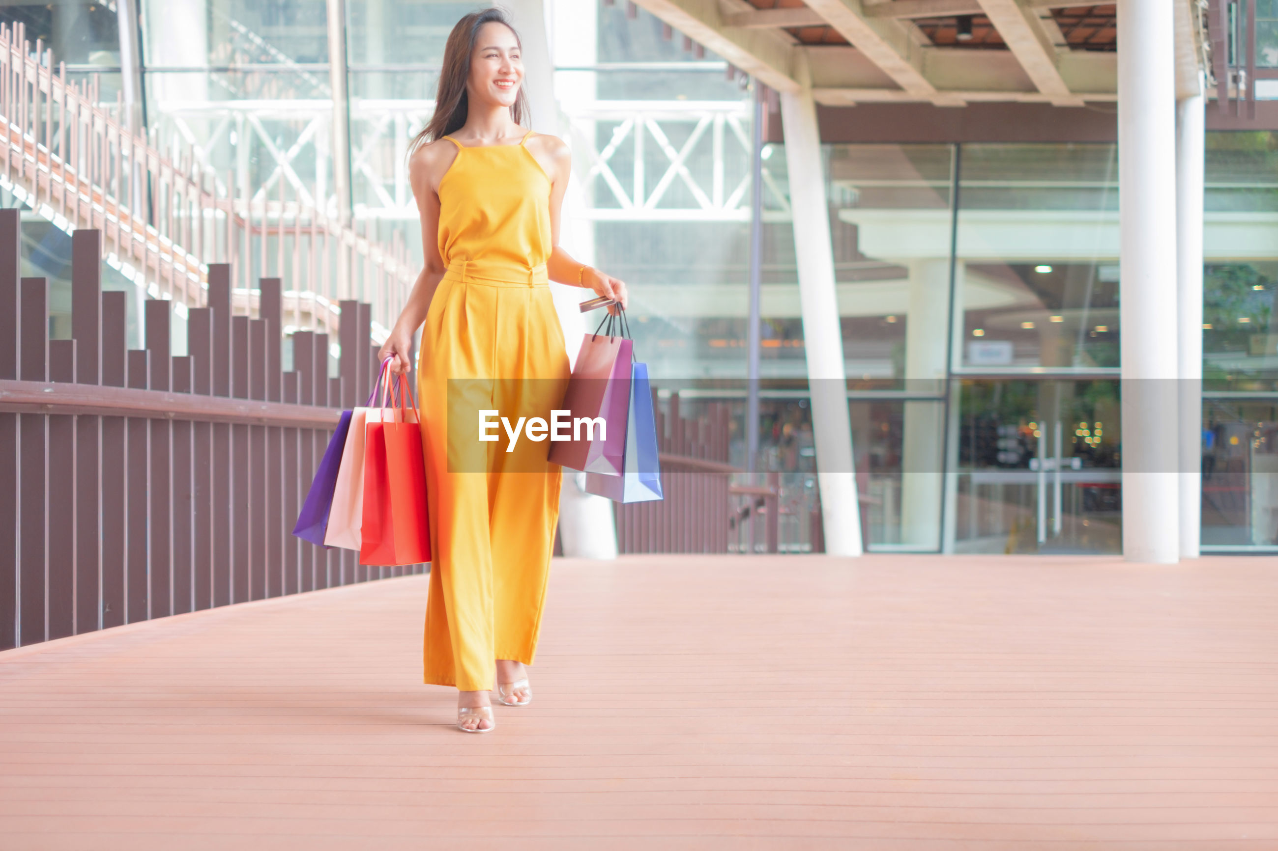 Young woman with bags walking in shopping mall