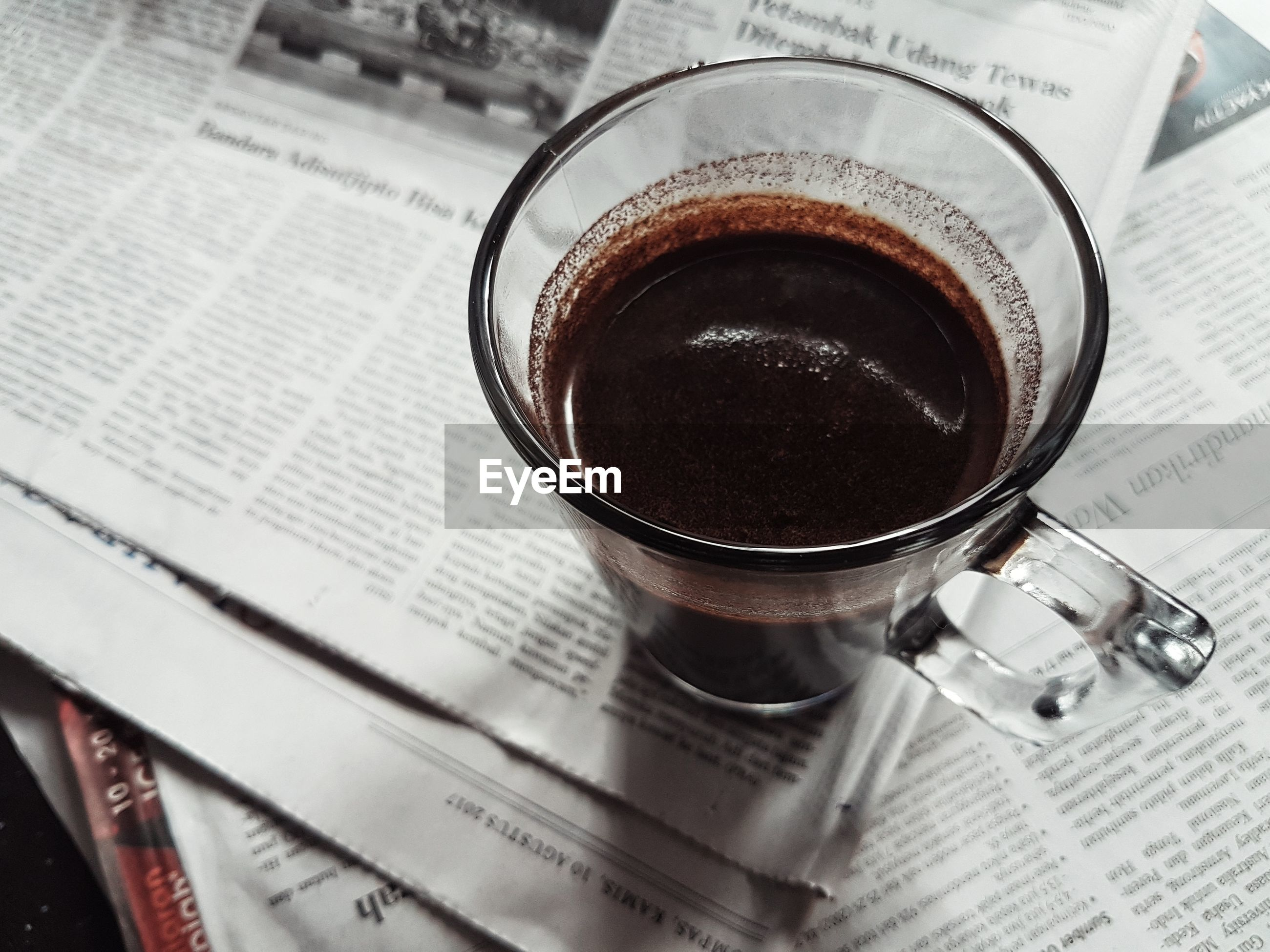 Close-up of coffee cup on newspaper