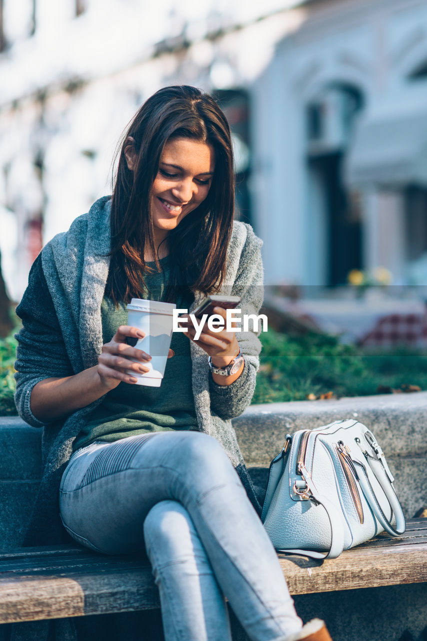 Smiling Young Woman Using Mobile Phone While Holding Disposable Cup In City