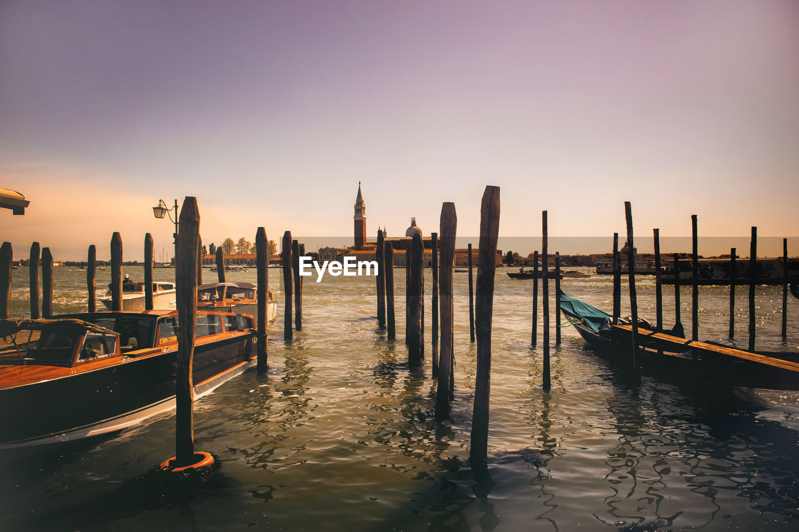 Gondolas amidst wooden posts in grand canal against sky