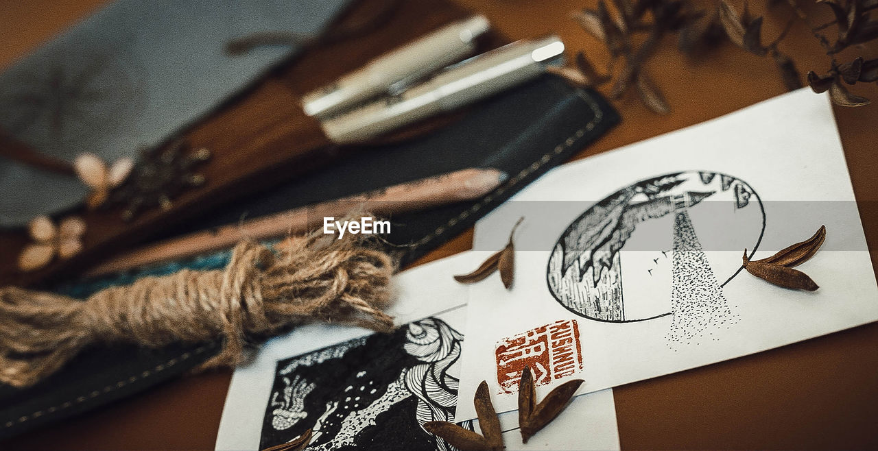 creativity, art and craft, indoors, representation, still life, paper, table, close-up, no people, craft, sketch, drawing - art product, high angle view, selective focus, focus on foreground, human representation, design, text, pattern
