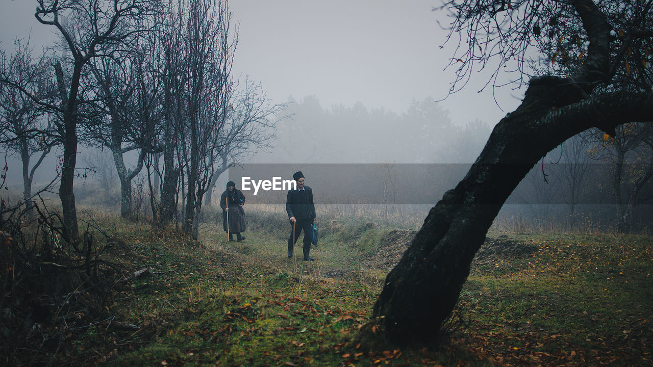 tree, fog, plant, land, real people, nature, men, two people, field, lifestyles, leisure activity, sky, bare tree, tranquility, walking, people, day, rear view, standing, outdoors