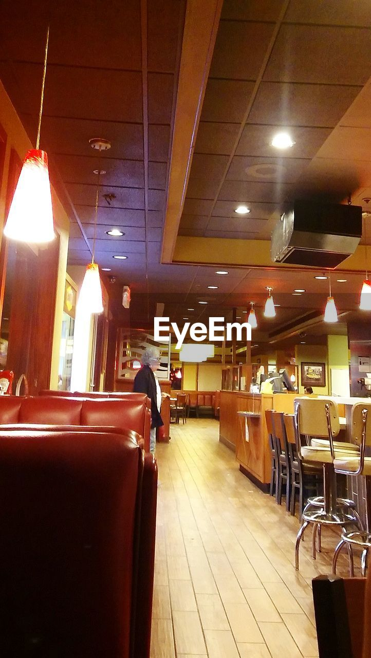 indoors, restaurant, illuminated, table, real people, men, chair, women, night, one person, people
