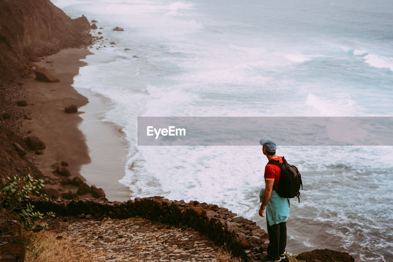 Side View Of Backpacker Looking At Sea While Standing On Cliff