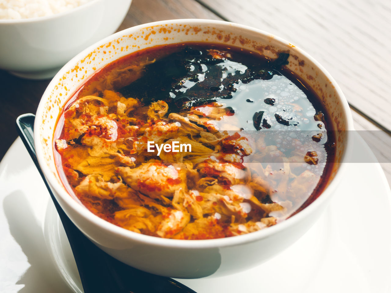 Asian cuisine - kimchi soup in white bowl with rice. close up photo.