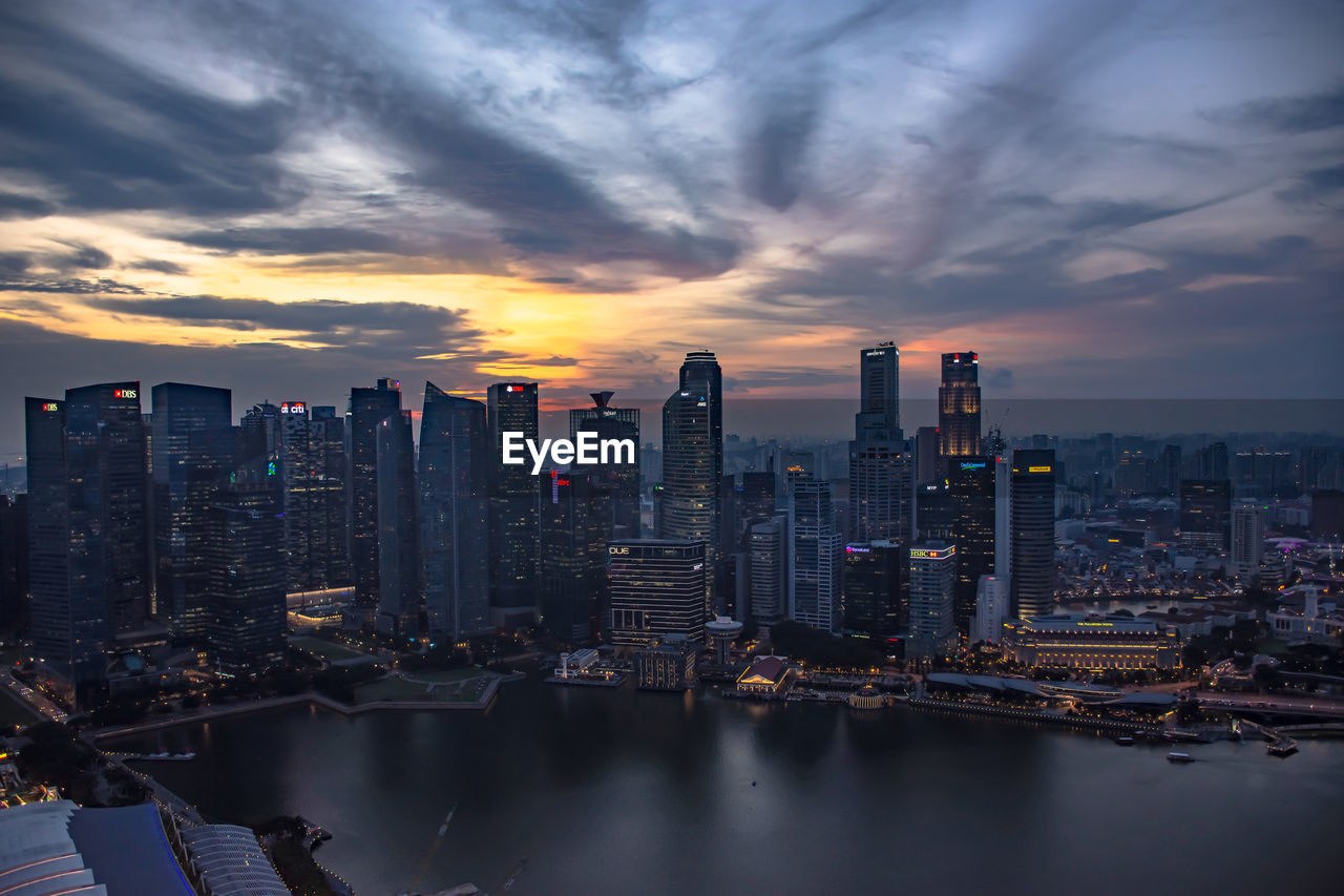 Aerial view of buildings by river against cloudy sky during sunset