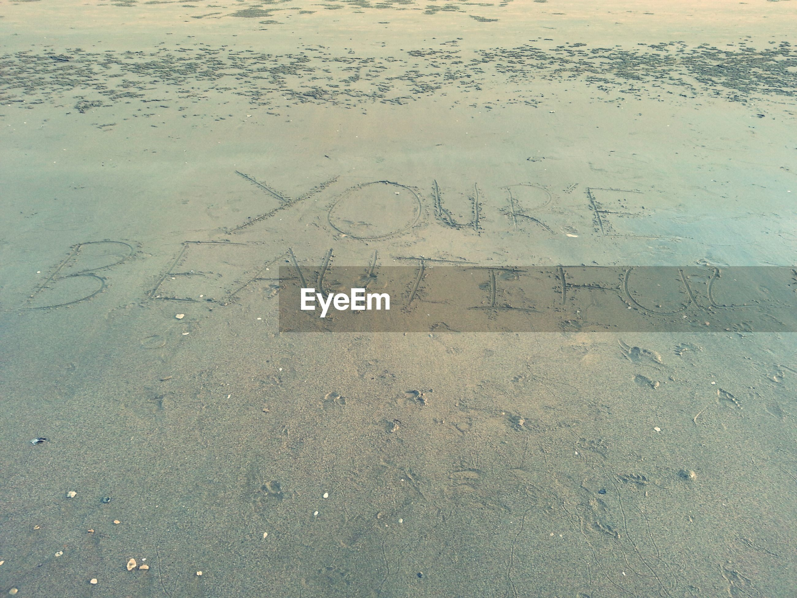 text, western script, sand, communication, beach, full frame, footprint, textured, high angle view, backgrounds, no people, day, close-up, outdoors, capital letter, shore, wall - building feature, wet, water, nature
