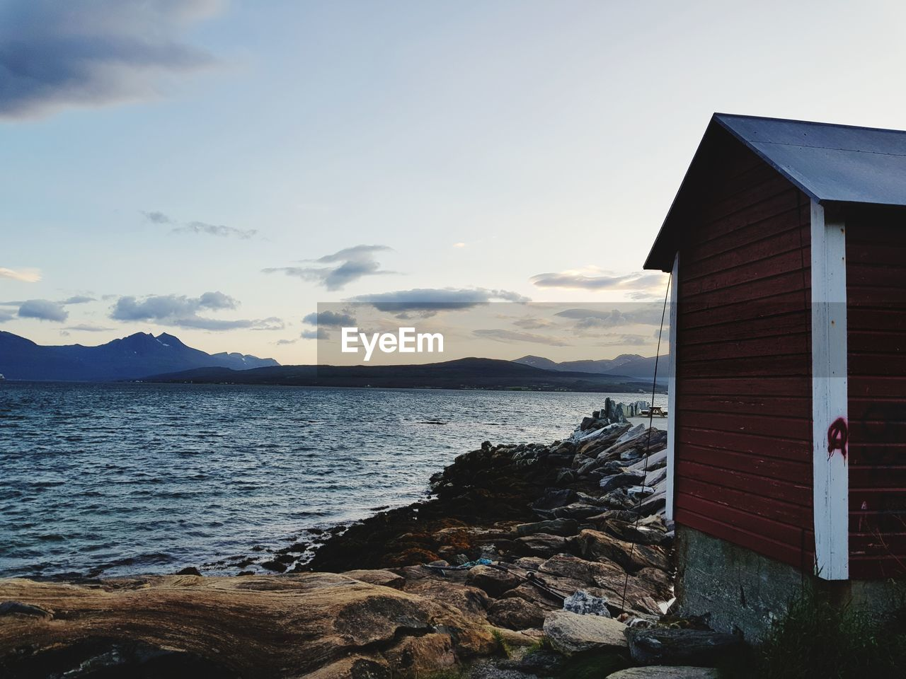 water, sky, built structure, architecture, cloud - sky, sea, beauty in nature, scenics - nature, tranquility, beach, tranquil scene, nature, land, building exterior, house, no people, rock, building, mountain, outdoors, cottage, cabin