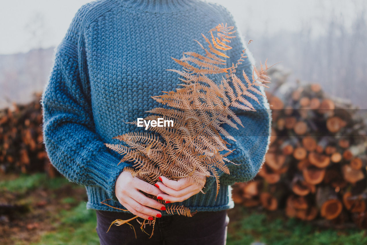 real people, focus on foreground, one person, leisure activity, lifestyles, casual clothing, day, nature, midsection, clothing, winter, field, land, standing, adult, holding, warm clothing, plant, women, outdoors, jeans, human limb