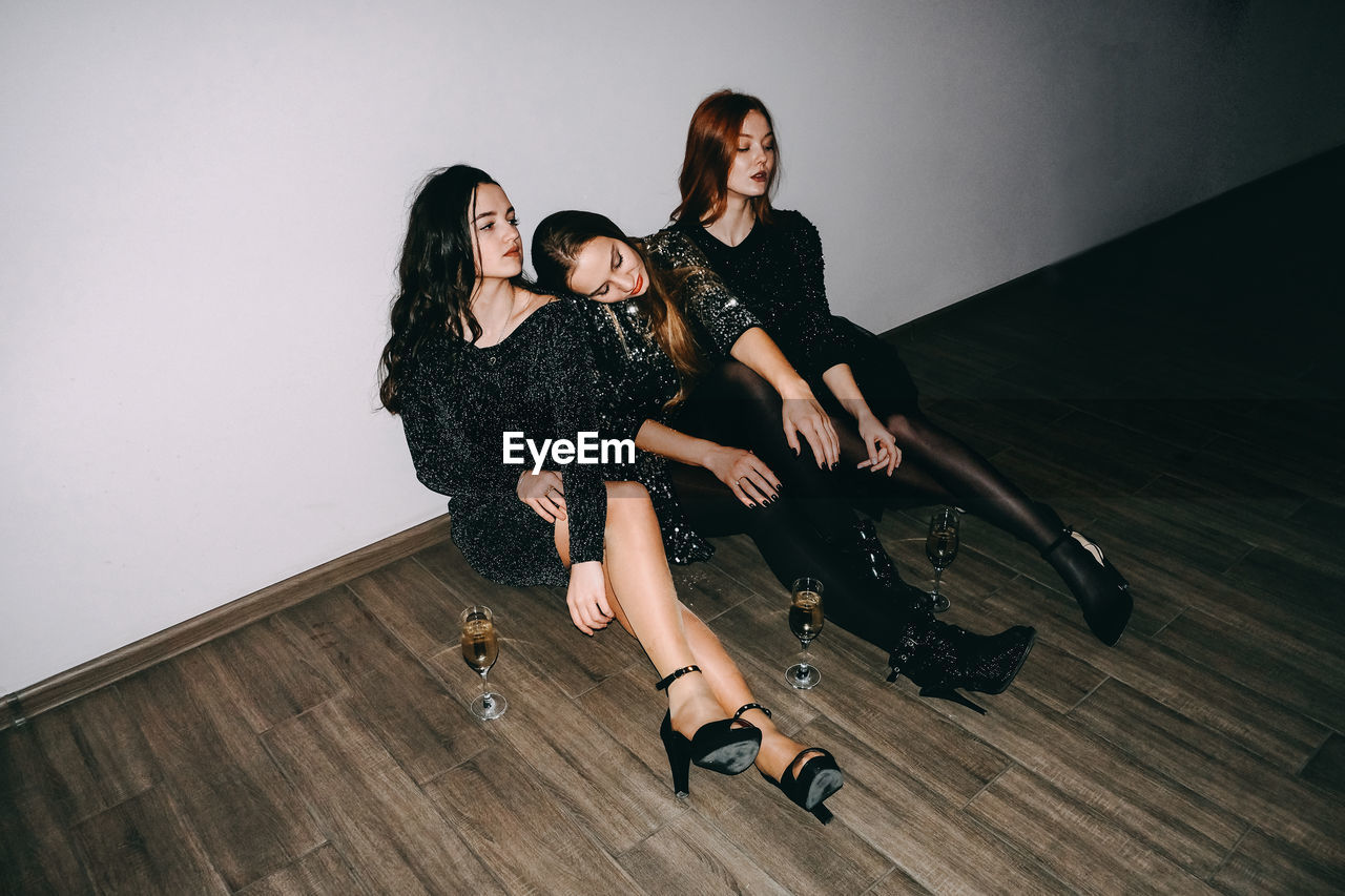 Full length of friends sitting on hardwood floor