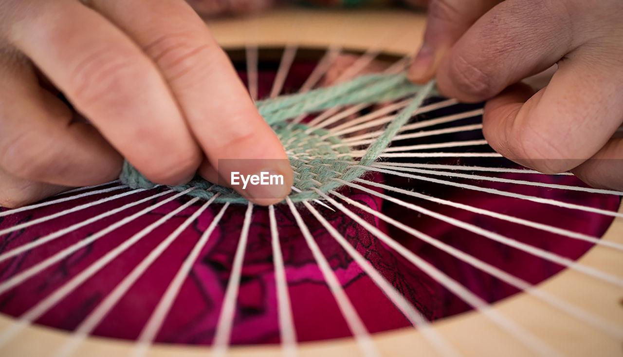 Close-up of hands making artwork