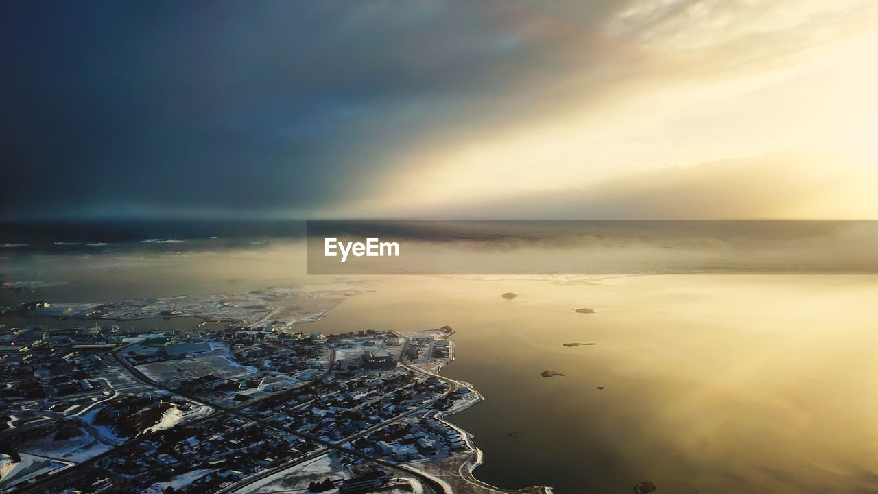 Aerial View Of Buildings And Sea Against Sky During Sunset