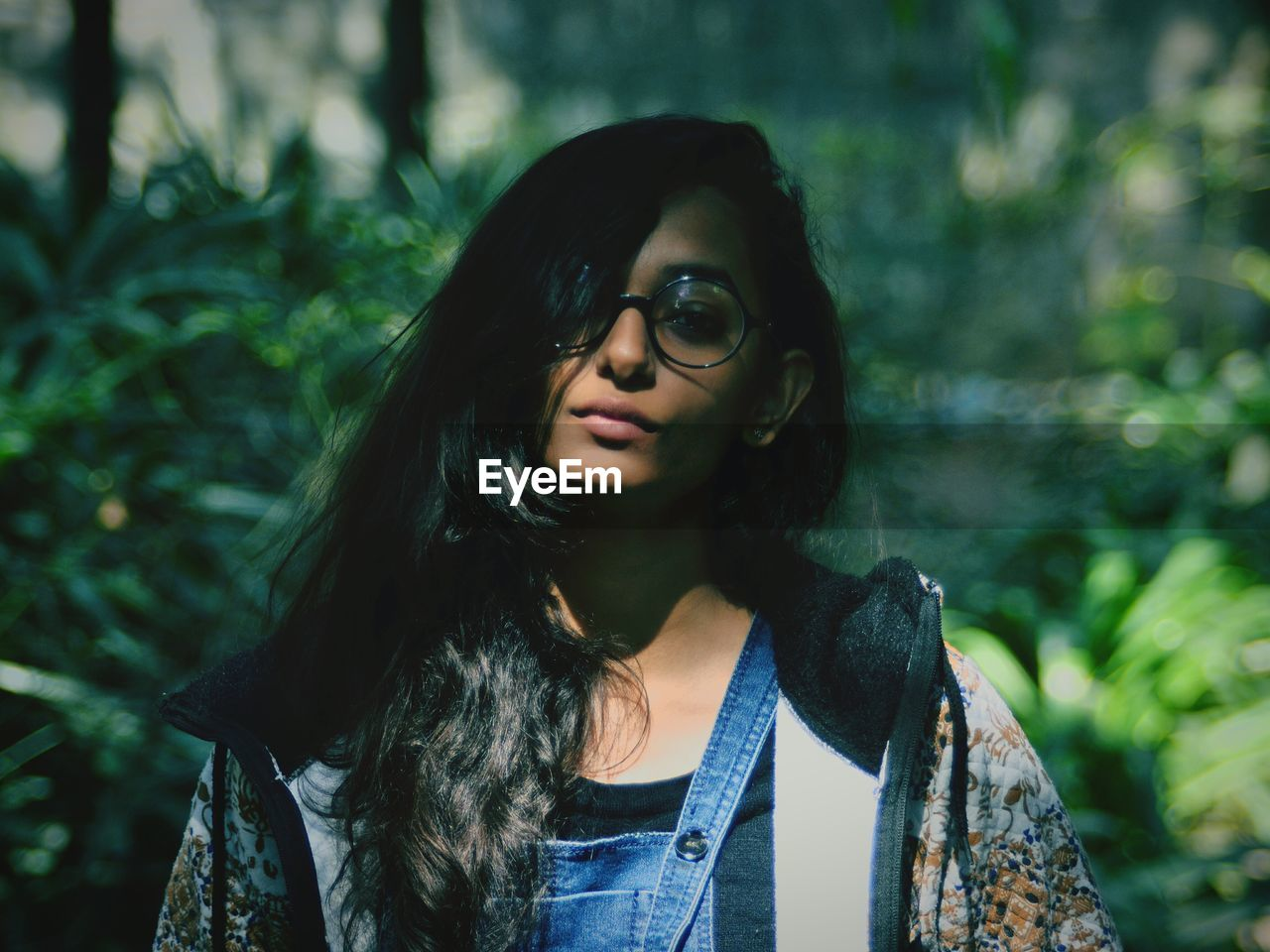 Portrait Of Young Woman Wearing Eyeglasses While Standing Against Plants