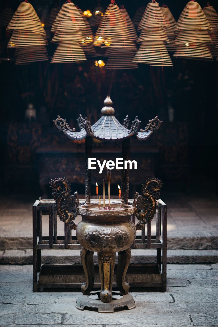 illuminated, table, lighting equipment, no people, burning, focus on foreground, belief, architecture, religion, place of worship, candle, spirituality, indoors, flame, built structure, wood - material, business, building, art and craft, electric lamp