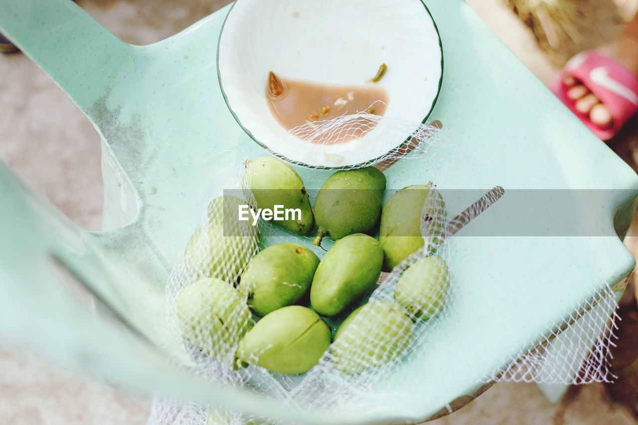 High Angle View Of Unripe Mangoes By Shrimp Paste On Table