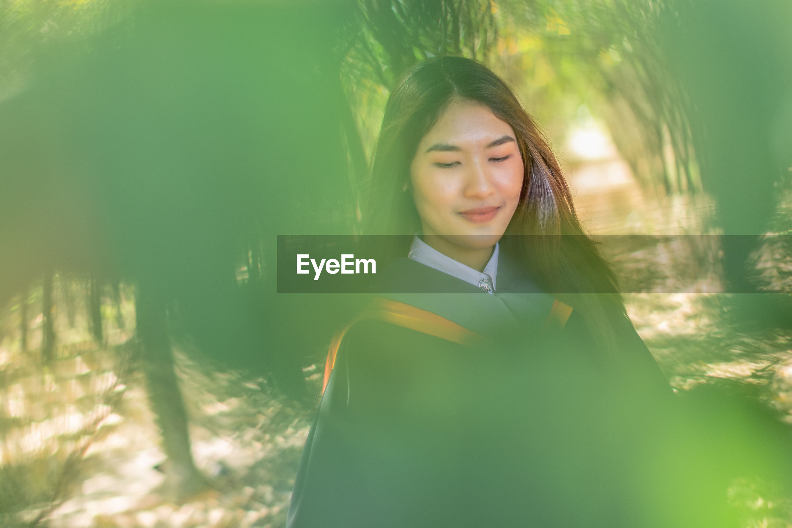 Smiling young woman with eyes closed standing in forest