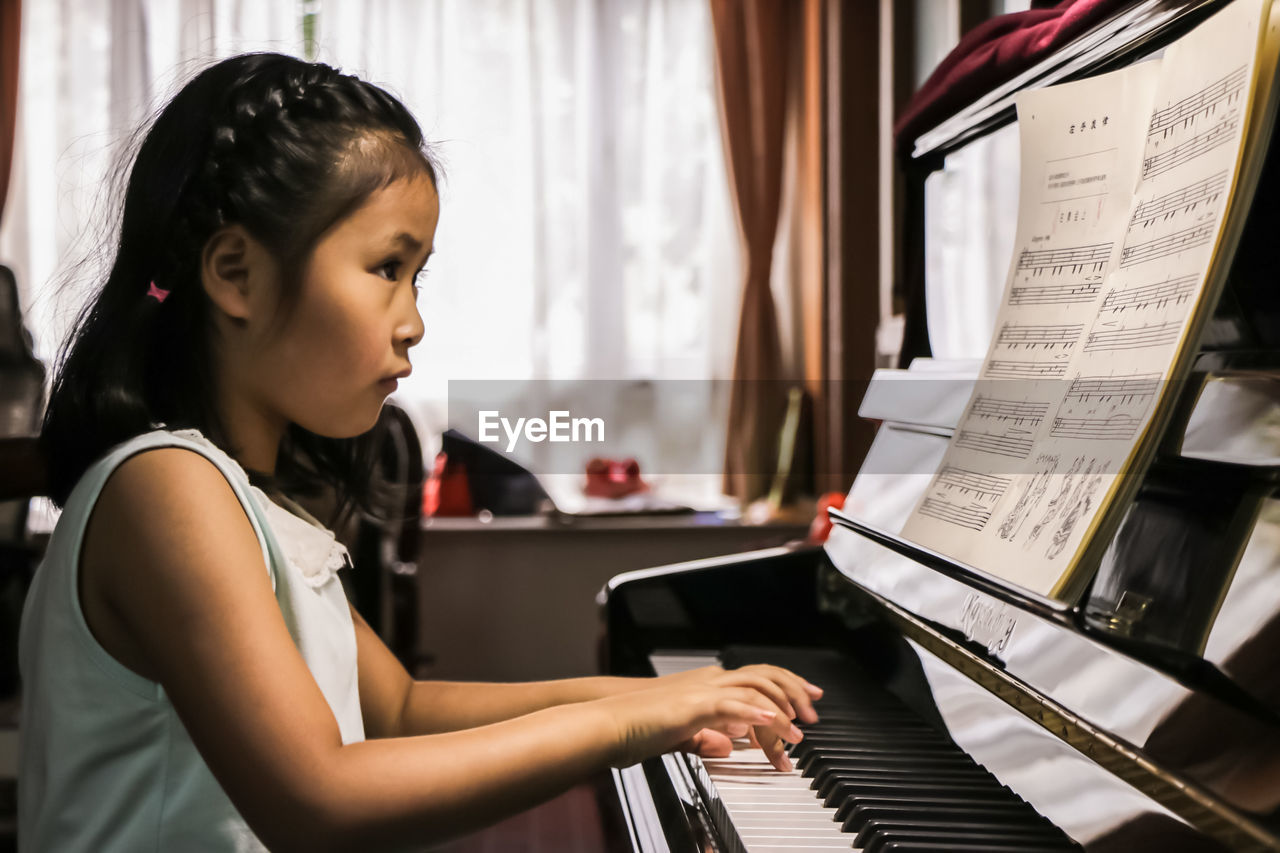 piano, music, musical instrument, playing, pianist, keyboard instrument, sheet music, piano key, practicing, skill, arts culture and entertainment, indoors, one person, musician, childhood, learning, concentration, musical note, real people, performance, leisure activity, education, sitting, lifestyles, classical music, close-up, day, people