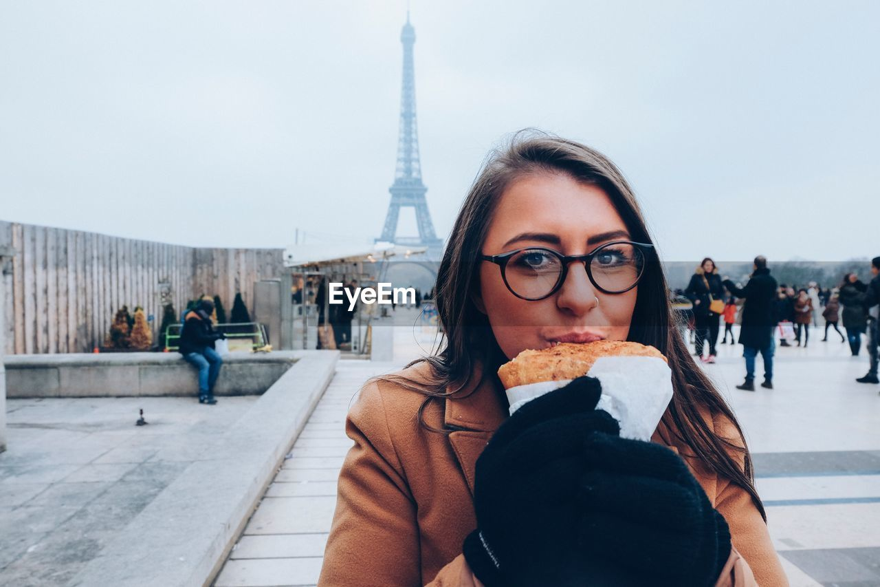 Portrait Of Young Woman Eating While Standing Against Eiffel Tower In City