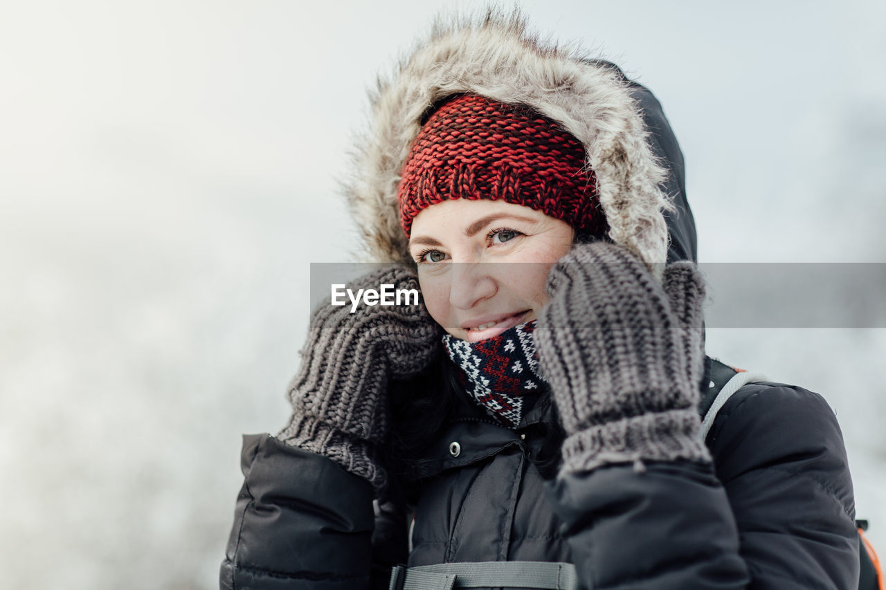 Close-Up Of Smiling Woman Wearing Warm Clothing