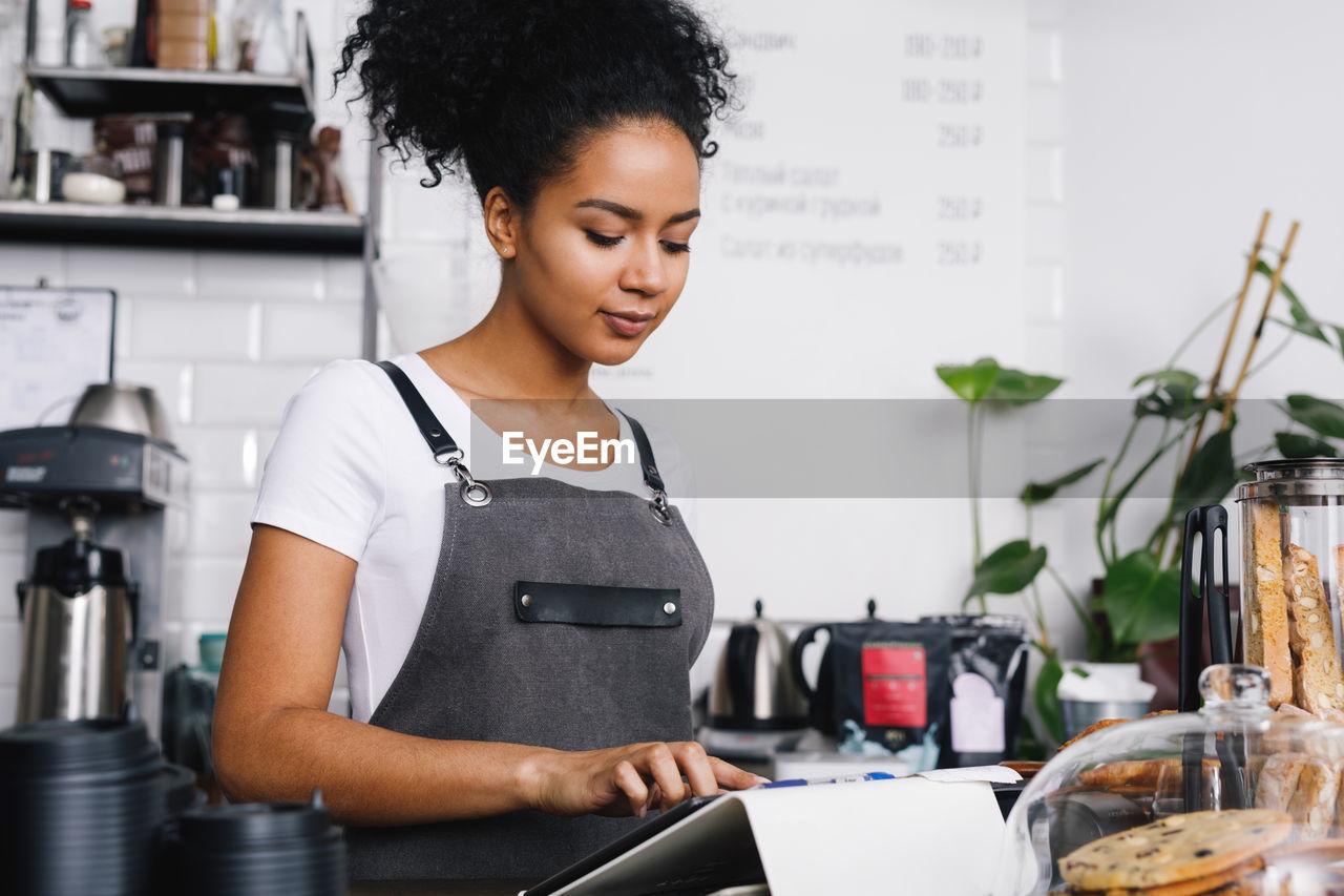 Barista Using Digital Tablet At Cafe
