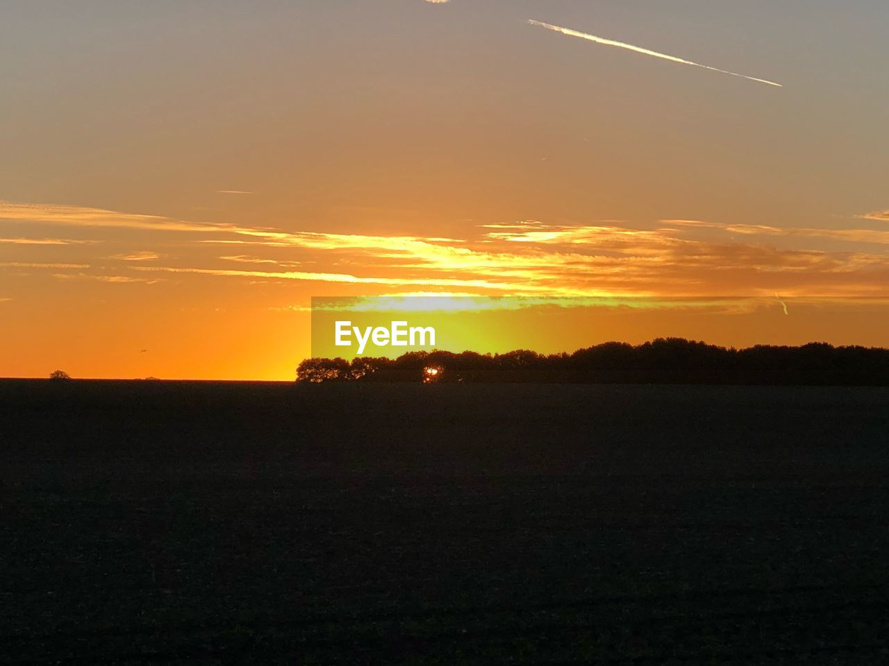 sunset, sky, beauty in nature, scenics - nature, tranquil scene, landscape, tranquility, orange color, environment, field, land, nature, idyllic, no people, non-urban scene, silhouette, plant, sun, cloud - sky, rural scene, outdoors, vapor trail